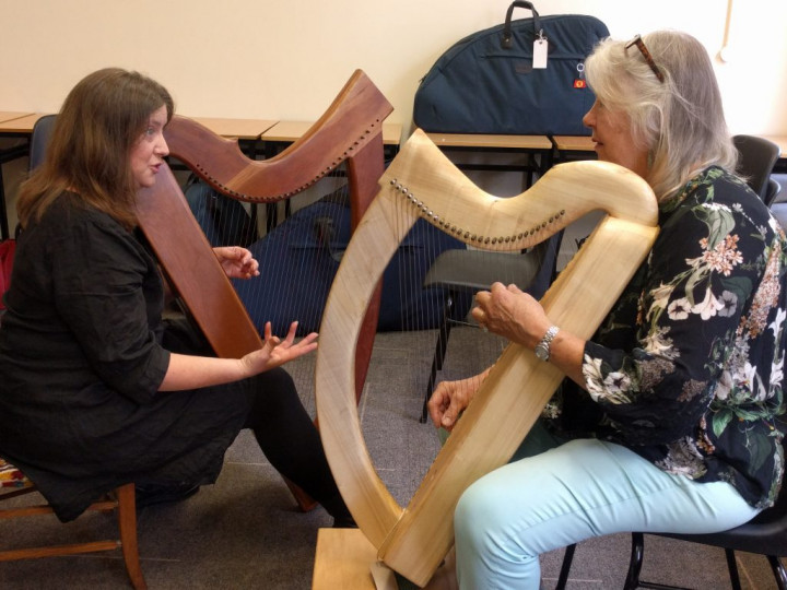 Two women with harps talking